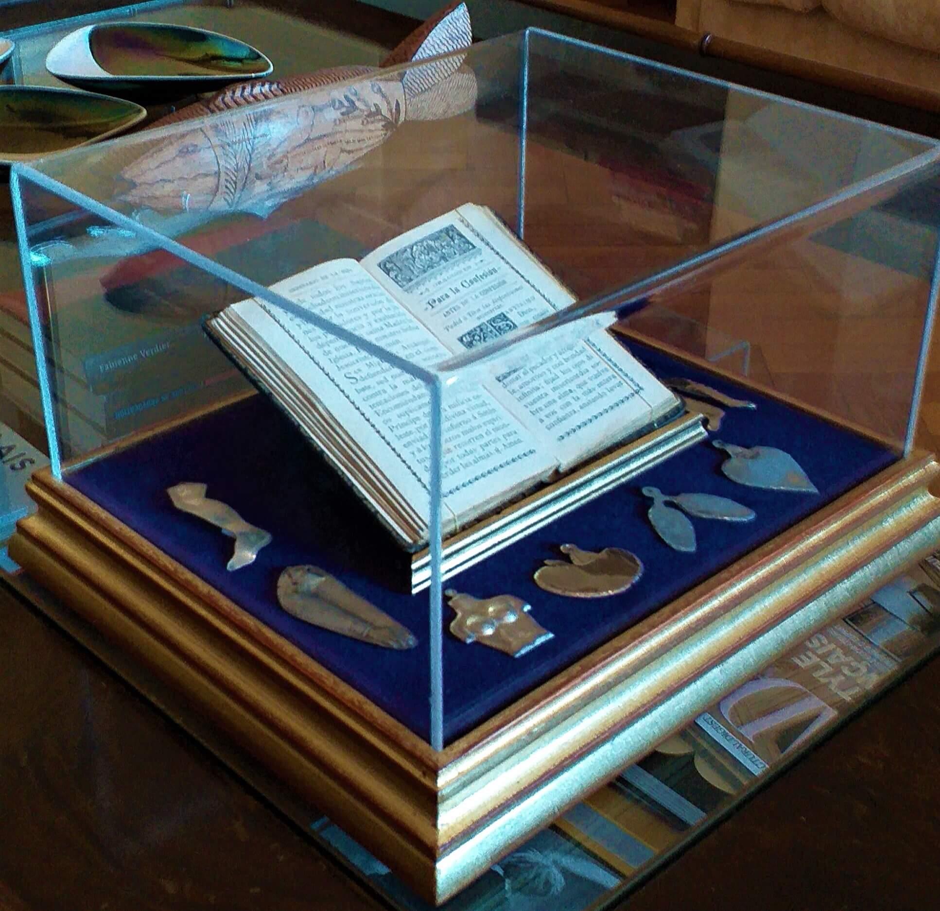«¿Dónde empieza y termina el cuerpo? Notas sobre la letra y la carne » caja de madera con tapa de acrílico transparente, forrada en terciopelo, misal antiguo y exvotos en plata y acero, 31 x 27 cm, 2020.